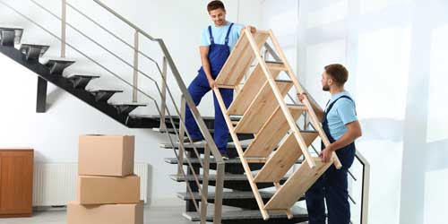 Transport mebli. Wnoszenie drewnianego regału po schodach w Krakowie